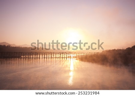 Wooden bridge over the river at sunrise was built by Mon Buddhist lineage of timber from the rain forest Length 850 meters across the river Tsonga lick in Sangklaburi Kanchanaburi of Thailand.  - stock photo