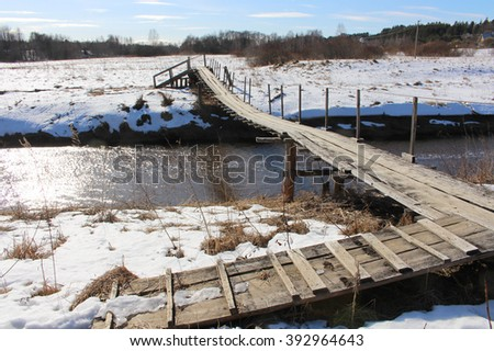 Wooden bridge over the river in the winter countryside