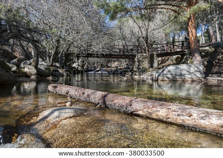 Wooden bridge over the river Manzanares along its course through La Pedriza, in Guadarrama Mountains National Park, Madrid, Spain - stock photo
