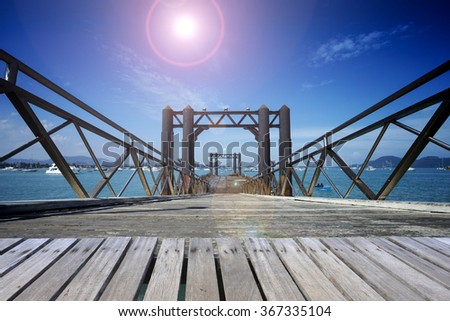 Wooden bridge over tropical, sea and lens flare.