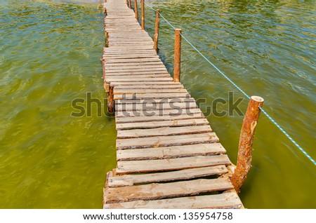 wooden bridge over water - stock photo