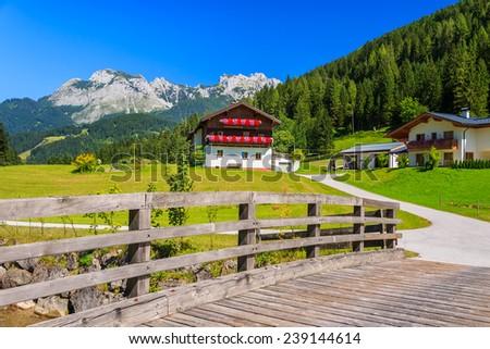 Wooden bridge to alpine village in summer, Austria - stock photo