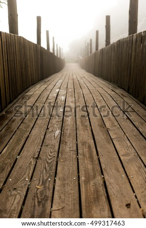 Wooden bridge with many planks and dense fog