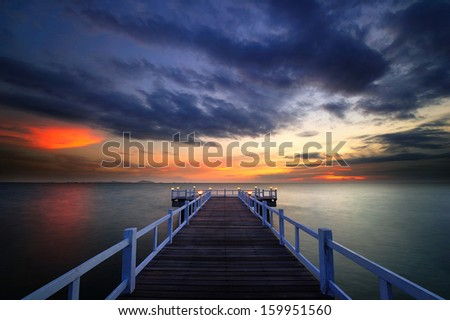 Wooden Bridge with the sunset and clouds - stock photo