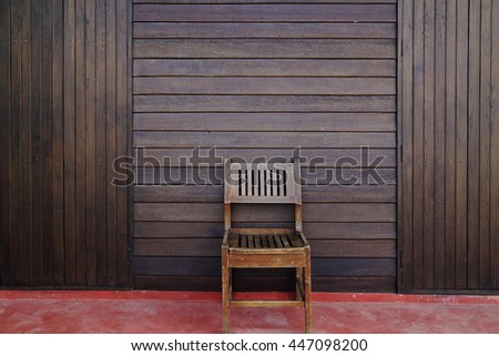 Wooden Brown chair against dark brown wall - stock photo
