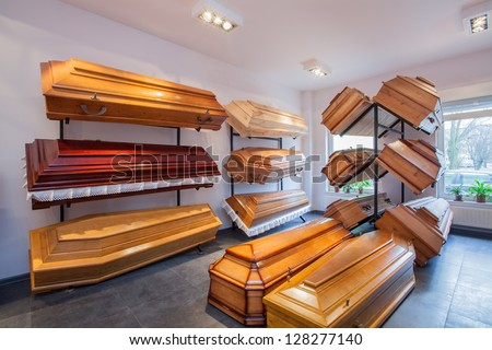 Wooden brown coffins in a funeral home - stock photo