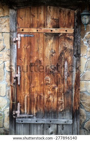 Wooden brown door with metal finish in a wall of masonry in vintage style, vertical picture - stock photo