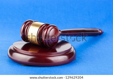 Wooden brown judges gavel on blue table background - stock photo
