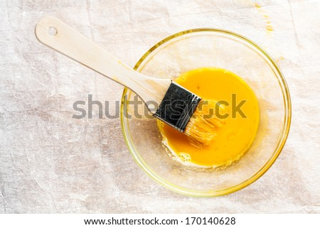 Wooden brush dipped into the whisked egg white and egg yolk in a small glass bowl during preparation of pastry  - stock photo