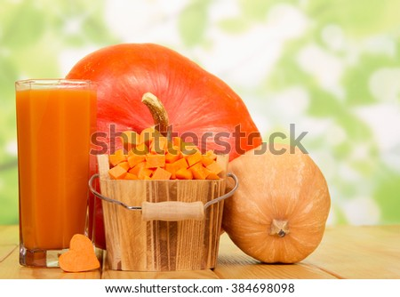 Wooden bucket with slices of ripe pumpkins and a glass of juice from them on an abstract green background. - stock photo