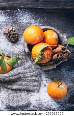 Wooden bucket with tangerines and cinnamon sticks over wooden background with snow and cone. Top view. - stock photo