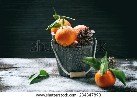Wooden bucket with tangerines over wooden background with snow and cone. - stock photo
