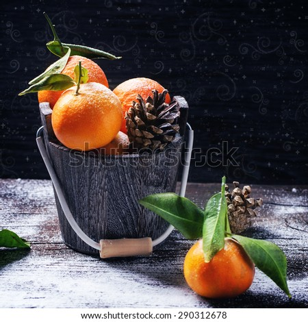 Wooden bucket with tangerines over wooden background with snow and cone. Square image - stock photo