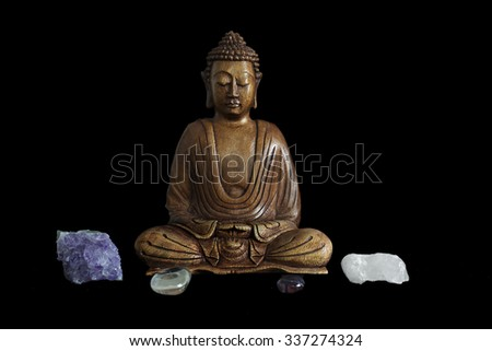 Wooden buddha statue with crystals on black background