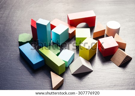 Wooden building blocks on a black - stock photo
