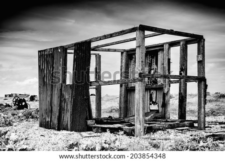 Wooden building that is badly dilapidated in black and white. - stock photo