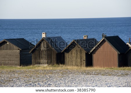 Wooden buildings with the Baltic Sea beyond in the fishing village of Helgumannen, along the coast of Faro Island, Sweden. - stock photo