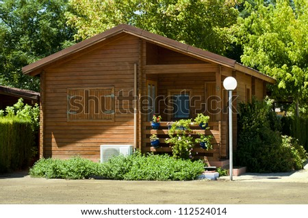 Wooden bungalow and garden - stock photo