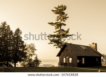 Wooden cabin by the lake, vintage photo - stock photo