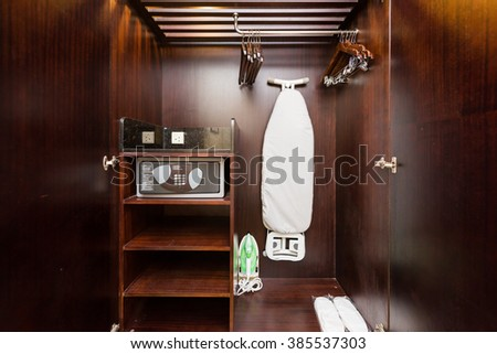 Wooden cabinet containing ironing board and security safe.