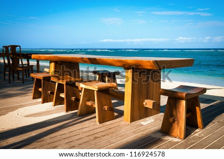 Wooden cafe table and chairs on a tropical beach on a tropical beach with blue sea on background - stock photo