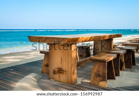 Wooden cafe table and chairs on a tropical beach with blue sea on background