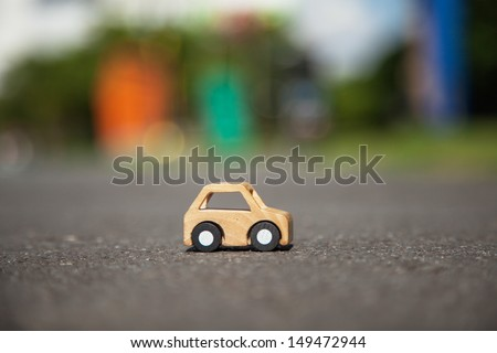 Wooden car model on the road. - stock photo