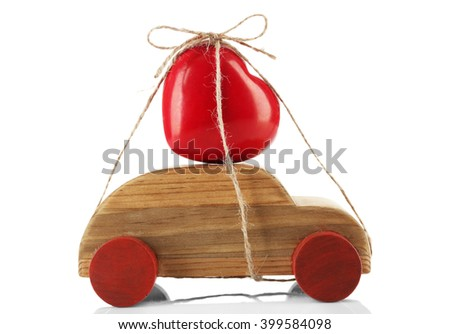 Wooden car with a red heart  tied to it, isolated on white