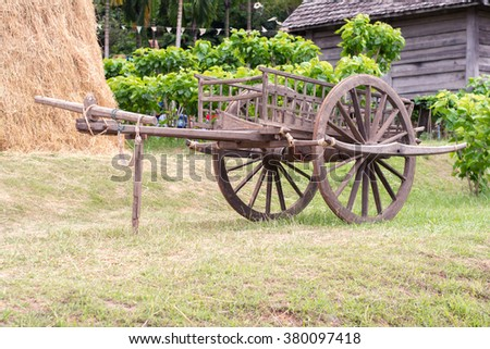wooden cart parked on the lawn next to a pile of straw at thailand
