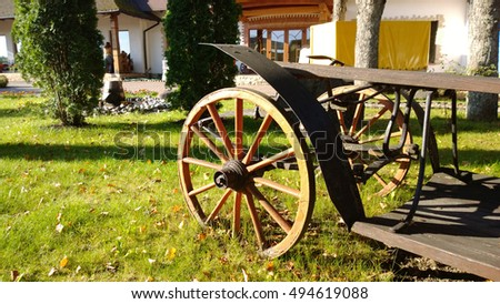 Wooden cart wheel on the grass in the Sunny autumn day