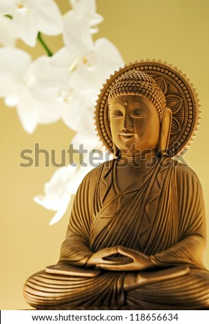 Wooden Carving of Buddha & White Orchids - stock photo