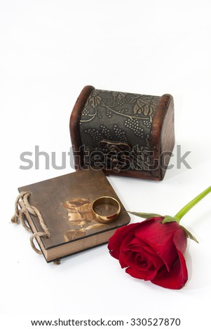 Wooden Case, red rose, notes and gold ring.