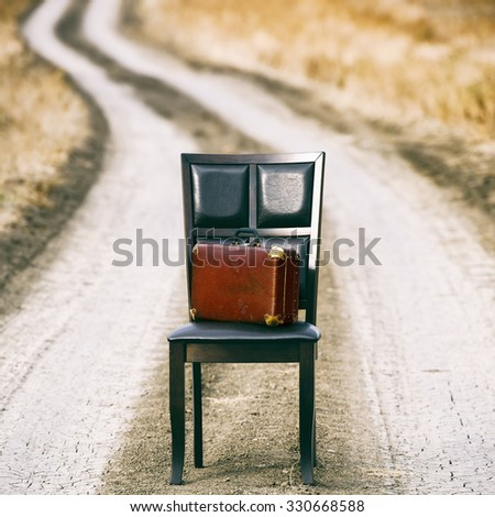 Wooden chair and old suitcase on the rural path