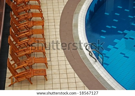 wooden chair and swimming pool