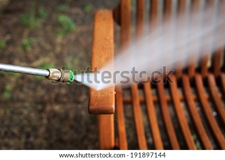 Wooden chair cleaning with high pressure water jet - stock photo