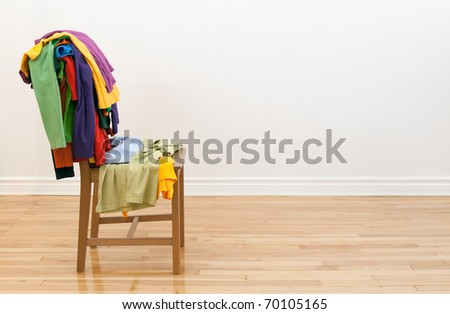 Wooden chair in a room, with lots of colorful messy clothes on it. - stock photo