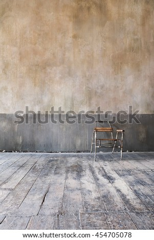 wooden chair in grungy interior. Loneliness, estrangement, alienation concept.