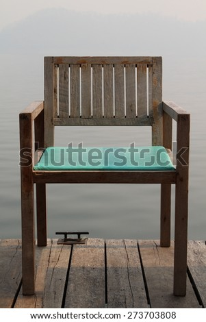 Wooden chair on wooden floor near the lake. - stock photo