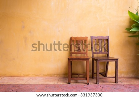 wooden chair seat and orange cement mortar wall background - stock photo
