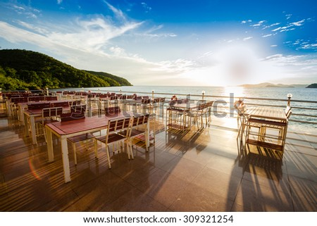 Wooden chairs and table on sea terrace restaurant against sunlight   - stock photo