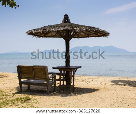 Wooden chairs and umbrellas on white beach at Koh Chang island, Thailand - stock photo