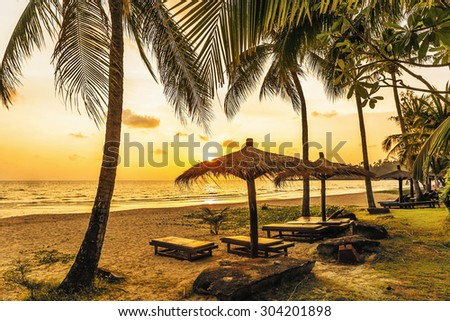 Wooden chairs and umbrellas on white beach in sunset time at Koh Chang island, Thailand - stock photo
