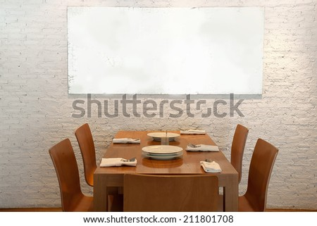 wooden chairs and wooden table  on white brick wall - stock photo