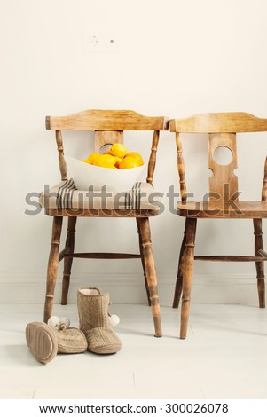 Wooden Chairs in the room, oranges and house slippers, toned - stock photo