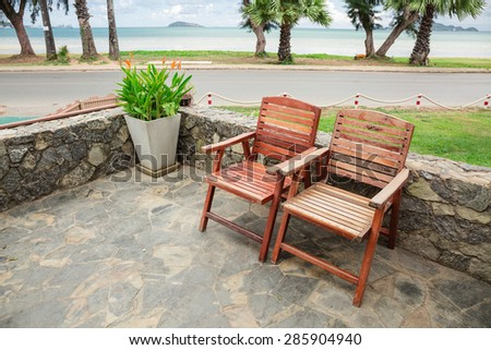 Wooden chairs on stone terrace beach in summer
