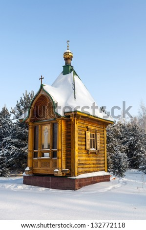 Wooden chapel in winter forest - stock photo