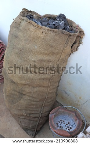 wooden charcoal in sacks with old stove - stock photo