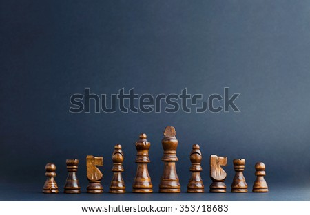 Wooden chess figurines organized in a row over black background