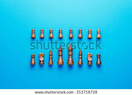 Wooden chess figurines organized in a row over blue background - stock photo