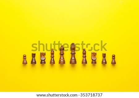 Wooden chess figurines organized in a row over yellow background